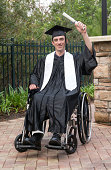 Vertical image of a new graduate in a wheelchair holding his diploma proudly